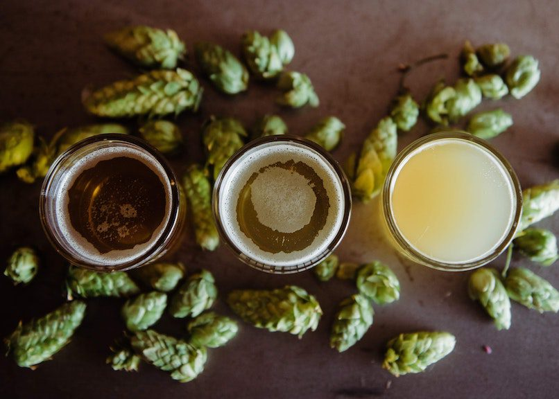 photo of glasses of beer with hops on table at farmhouse breweries