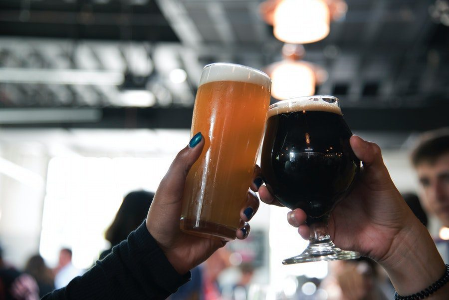 photo of two hands holding glasses of beer at breweries in eugene