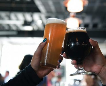 two hands toasting with glasses of beer at breweries in Eugene